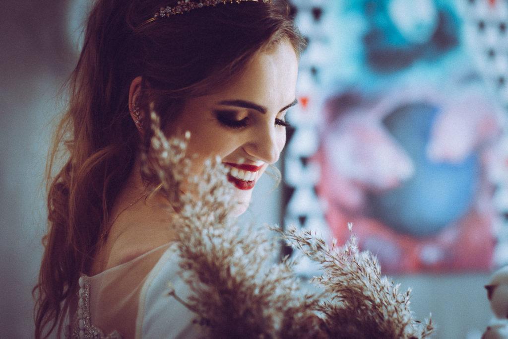 Uśmiechnięta Panna Młoda schowana za bukietem kwiatów