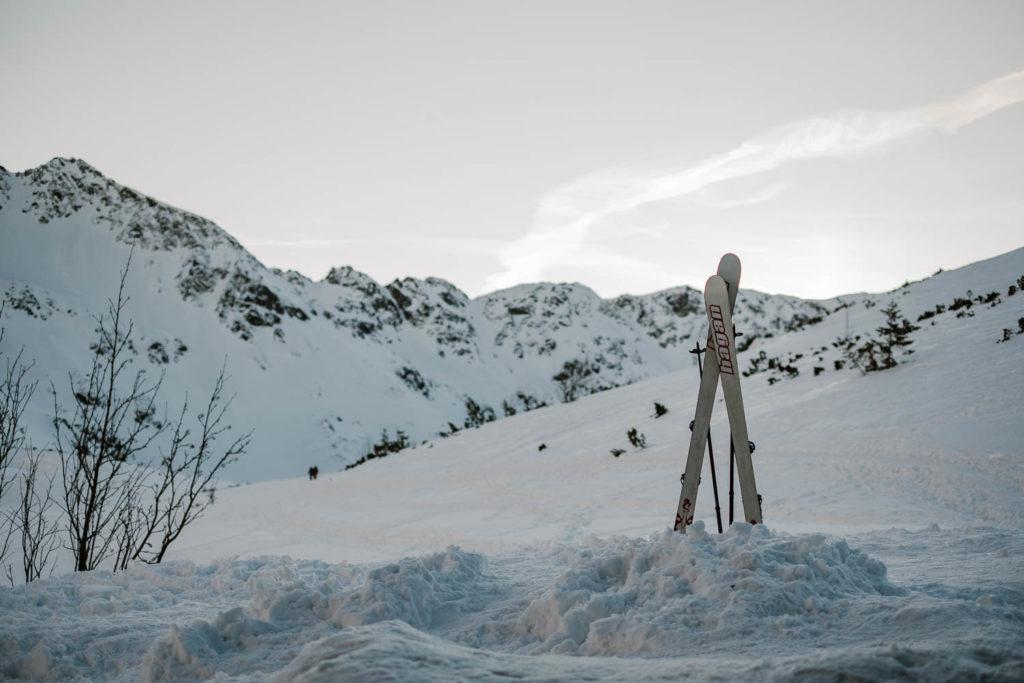 Wieczór w Schronisku w Dolinie Pięciu Stawów Polskich. Skrzyżowane i wbite w śnieg narty przed schroniskiem.