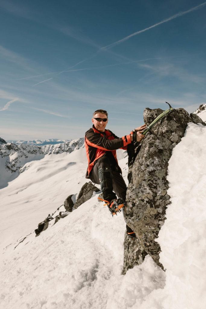 Grzegorz wariuje i wspina się z czekanem na skałę na szlaku na Kozi Wierch.