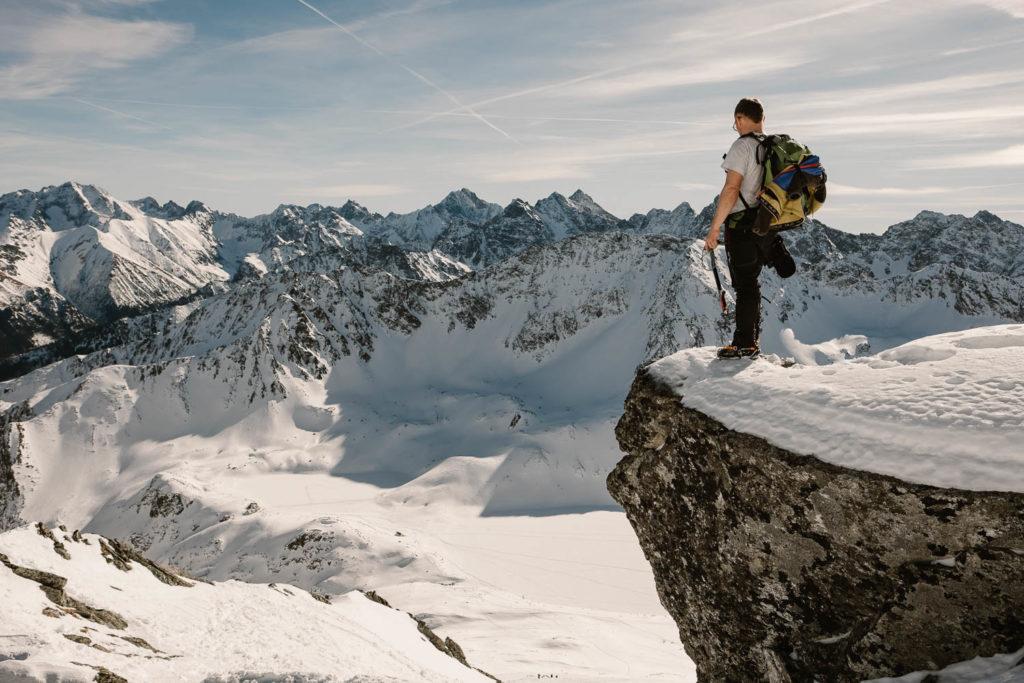 Marcin stoi na skale patrzy w dół, w kierunku Doliny Pięciu Stawów Polskich.