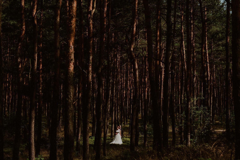 Liliana i Łukasz między drzewami.